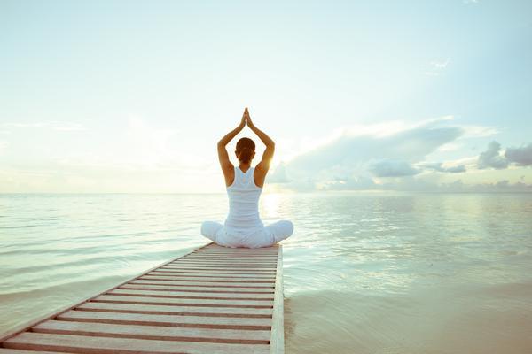 Hormone im Gleichgewicht - Frau meditiert an einem Bergsee