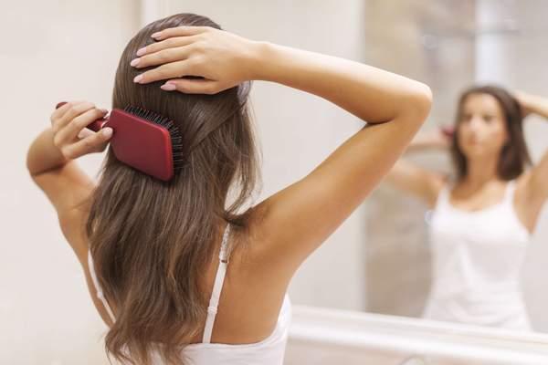 Frau pflegt schöne gesunde Haare vor Spiegel