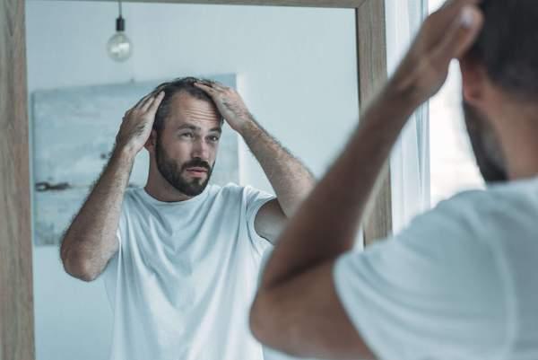 Mann prüft Haarausfall im Spiegel