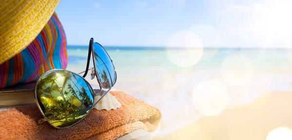 Sonnenbrille, Handtuch und Hut am Strand